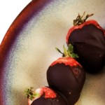Chocolate covered strawberries on ceramic brown plate on white background