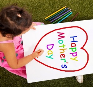 Child making Mother's Day sign